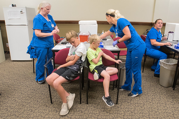 Leo DeMars (white shirt), 11, and Milo DeMars (green shirt), 6, inspect their arms as Linda Othoutt (left) and Katie Hiller prepare their flu shots in the community room at River Hills Mall on Tuesday. Photo by Jackson Forderer