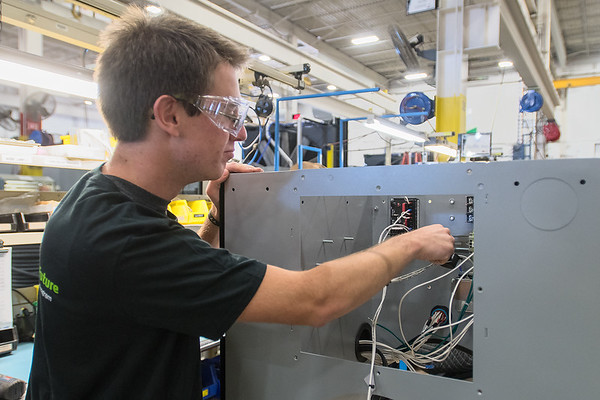 Ethan Dempster, a senior at Mankato East High School, shows how he installs components in an outlet box at MTU Onsite Energy on Wednesday. Photo by Jackson Forderer