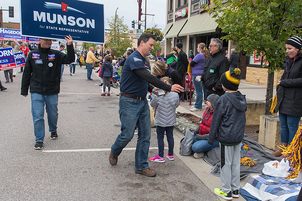 State Representative Jeremy Munson (center) hands out stickers as he campaigned along Front St. with the Minnesota State University homecoming parade. Photo by Jackson Forderer