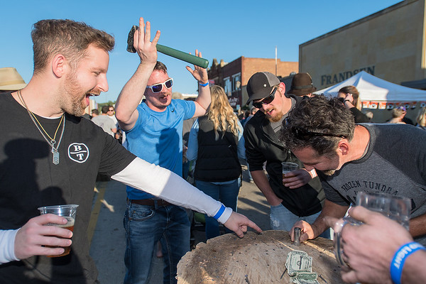 Derrick Ledeina (left) and Rick Ledeina (right) inspect a nail hit by Lance Wegener (second from left) during a game of hammerschlagen at Bier on Belgrade in North Mankato on Saturday. Bier on Belgrade also samples from local breweries and a main stage with music. Photo by Jackson Forderer