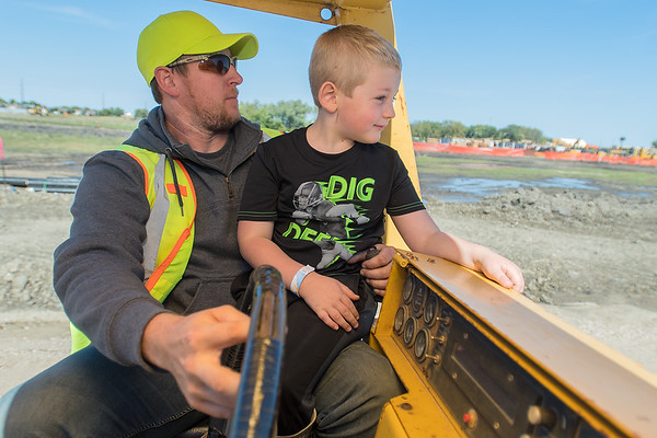 Josh Meger (right) looks out onto a path while Bill Drummer rides a steamroller as part of the Dig It! event held on Saturday. Photo by Jackson Forderer