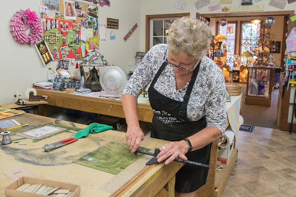 Dee Thomas, owner of Henderson Classical Glass, cuts a piece of glass for a decorative wedding invitation. Thomas has owned the business since 2004. Photo by Jackson Forderer