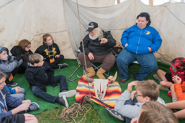 Minoc Scabby Robe Parnett (center) of the Blackfoot Tribe tells sixth-grade students from Prairie Winds Middle School a Native folk tale inside a teepee at Land of Memories Park on Friday. Parnett's folk tale was just one of many educational sessions held on Friday as part of the 46th annual Mahkato Mdewakanton Powwow. Photo by Jackson Forderer