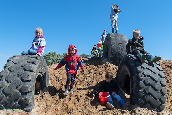 Children play on a giant sand hill and playground that was created for the Dig It! event on Saturday. Photo by Jackson Forderer