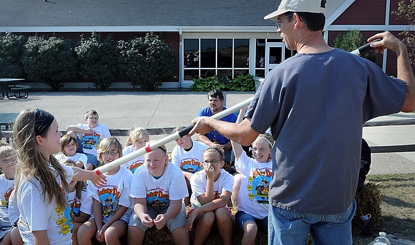 Janesville veterinarian Troy Summers demonstrates an animal restraining device on Janesville-Waldorf-Pemberton fifth grader Katelyn Losee at a Farm and Home Safety Camp Tuesday at Farmamerica near Waseca. An estimated 285 students from several area schools were expected to attend the 15th annual event.