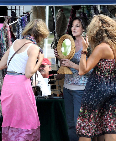 Mary Lue's Yarn and Ewe's Peggy Grey holds a mirror for a customer trying on a scarf during Saturday's Rock Bend Folk Festival.