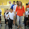 Loyola High School senior Jessi VanBlarcom escorts Loyola kindergartener Joaquin Collram on Wednesday to the annual all-school picnic following mass. The picnic was moved indoors because of the rain.