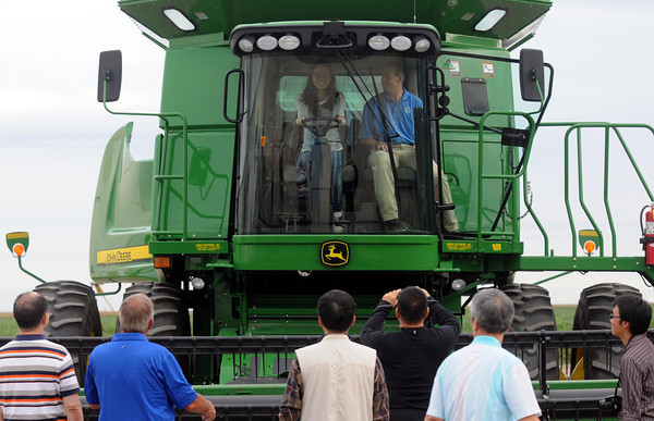 Pat Christman<br /> The Minnesota Soybean Growers Association's Sam Ziegler shows a representative of one of Taiwan's soybean import companies the inner workings of a combine during a tour of the Earl and Lynette Ziegler farm near Good Thunder. A group of 9 representatives from Taiway were touring Minnesota to lear about the latest trends in soybean research and production.