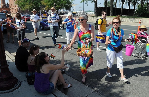 Pat Christman<br /> Marchers hand out rainbow colored flags during Saturday's Pridefest parade along Riverfront Drive.
