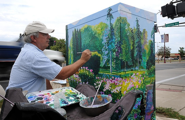 John Cross<br /> Bill Bukowski turns a traffic signal box at the intersections of Cherry Street and Riverfront Drive into a scene from the Sibly Park garden. Bukowski, an art professor at Bethany Lutheran College, was one of 10 artists selected to turn the gray boxes found around the city into artwork.