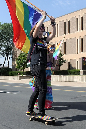 Pat Christman<br /> Hannah Aasum (on skateboard) and Debbie Ristau carry flags along Saturday's parade route.