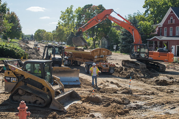 Mark Hobday (center) walks over to talk to Pat Roch in a caterpillar as Ron Vadnerhurr (right) uses a backhoe to load dirt into a truck to be hauled away at the intersection of East Main St. and 5th St. in Mankato on Friday. Photo by Jackson Forderer