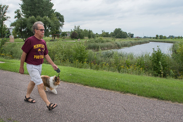 Ken Schrader walks his dog Khloe through Benson Park in North Mankato. Schrader said he walks his dog through the park at least once a day if not more. Photo by Jackson Forderer