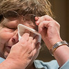 Nancy Kennedy wipes a tear away from her eye while reading a poem she wrote in memory of her father who passed away last year. Kennedy, along with others of the Aktion Club Theater Poets, a special needs performing arts group, read poems they wrote at the Performing Arts Center on the Minnesota State campus on Wednesday. Photo by Jackson Forderer