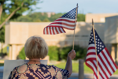 Carol Rath waves the American flag to traffic passing by as she and others protested along Riverfront Avenue on Wednesday. Photo by Jackson Forderer
