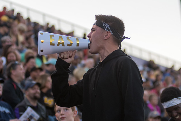 Koby Gagnon, a senior at Mankato East, leads the parent section in a cheer in the first half of Friday's Mankato East versus Mankato West football game. Photo by Jackson Forderer