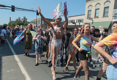 Mitchell Douglas (center) waves to people watching the Pride Parade along Riverfront Avenue on Saturday morning. Photo by Jackson Forderer