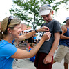 """Trish McCarthy, of Boulder, pins a bib number on her 9-year-old son Zach before the start of the kids race during the West End 3K on Thursday, July 19, on Pearl Street in Boulder. For more photos and video of the race go to  <a href=""""http://www.dailycamera.com"""">http://www.dailycamera.com</a><br /> Jeremy Papasso/ Camera"""