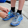"""Trish McCarthy, of Boulder, ties a timing chip to her son Zach's show before the start of the kids race during the West End 3K on Thursday, July 19, on Pearl Street in Boulder. For more photos and video of the race go to  <a href=""""http://www.dailycamera.com"""">http://www.dailycamera.com</a><br /> Jeremy Papasso/ Camera"""