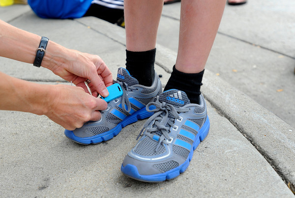 "Trish McCarthy, of Boulder, ties a timing chip to her son Zach's show before the start of the kids race during the West End 3K on Thursday, July 19, on Pearl Street in Boulder. For more photos and video of the race go to  <a href=""http://www.dailycamera.com"">http://www.dailycamera.com</a><br /> Jeremy Papasso/ Camera"