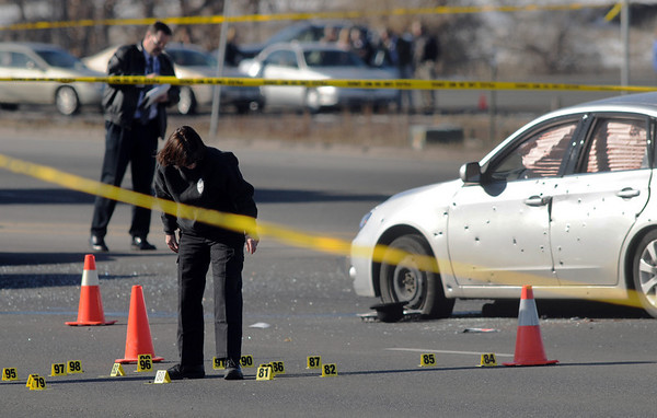 Broomfield Police criminalist Brenda Harris marks rounds at the scene of a Westminster Police shoot out at eastbound 120th Ave. and Federal Blvd. on Thursday.<br /> Two Westminster officers were shot in the gun battle. Federal is closed both directions from Federal Blvd. to Pecos St.<br /> November 19, 2009<br /> Staff photo/David R. Jennings