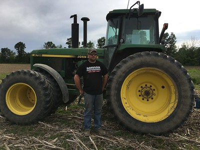ALYSSA ALFANO / GAZETTE Kyle Reusch, owner of Kruggel Farms, poses Wednesday next to his planter after working to find dry spots in his field to start planting soybeans.