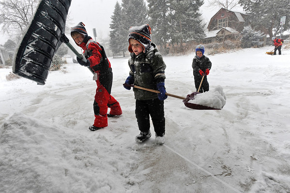 SNOW<br /> Left to right, Evan Sims and his brothers Connor and Grant create a pile of snow in their driveway while helping their mother, Alissa, background, shovel sidewalks in the neighborhood.<br /> Photo by Marty Caivano/Dec. 30, 2010