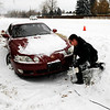 James Barr, 27, of Lafayette, works to tow his wife Ashley out of a ditch on South Boulder Road in Louisville during a snowstorm on Thursday, Dec. 30.<br /> Jeremy Papasso/Camera
