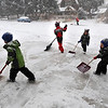 SNOW<br /> Left to right, Logan Sims and his brothers Evan, Connor and Grant shovel their driveway while helping their mother, Alissa, background, shovel sidewalks in the neighborhood.<br /> Photo by Marty Caivano/Dec. 30, 2010