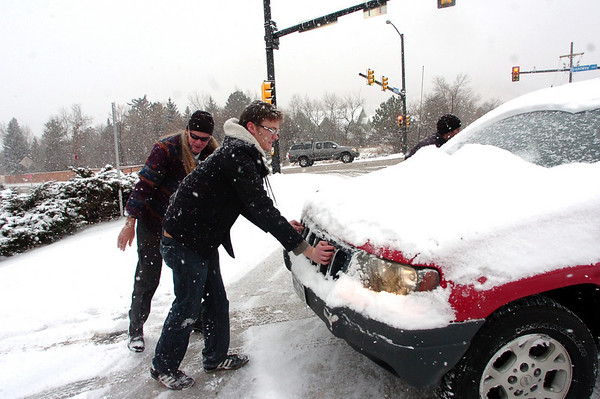 Dave King, left and Chris Maddox prepare to push a car that was stuck on a side road off Broadway in Boulder Thursday afternoon.<br /> Photo by Paul Aiken / December 30 2010
