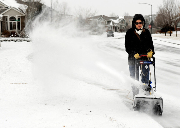 Lynda Dwornik, 61, of Lafayette, uses her electric snowblower to clear the sidewalk in front of her home on Blue Jay Way during a snowstorm on Thursday, Dec. 30.<br /> Jeremy Papasso/Camera