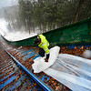 KRISTOPHER RADDER - BRATTLEBORO REFORMER<br /> Ryan Jones, of Evans Construction, rolls out a tarp down the inrun at the Harris Hill Ski Jump on Friday, Jan. 12, 2018 as they prepare the annual ski jump competition.