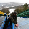 KRISTOPHER RADDER - BRATTLEBORO REFORMER<br /> Jeff Kneeland, of Evans Construction, hammers down the tarp on the inrun at the Harris Hill Ski Jump on Friday, Jan. 12, 2018 as they prepare the annual ski jump competition.