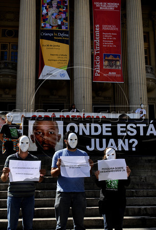 "People protest, in front of the Rio de Janeiro state Assembly, against the disappearance of Juan de Moraes, 11, a boy wounded during a gunfire between police and drug traffickers in the Danon slum, Rio de Janeiro, Brazil, June 29, 2011. Parents and human rights militants accuse the police for the disappearance. In the big banner says: ""Where is Juan?"". (Austral Foto/Renzo Gostoli)"