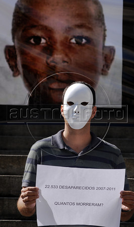 "People protest, in front of the Rio de Janeiro state Assembly, against the disappearance of Juan de Moraes, 11, a boy wounded during a gunfire between police and drug traffickers in the Danon slum, Rio de Janeiro, Brazil, June 29, 2011. Parents and human rights militants accuse the police for the disappearance. In the big banner says: ""22533 missings between 2007-2011. How much are dead?"". (Austral Foto/Renzo Gostoli)"