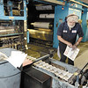 Record pressman Bob Tarnowski pulls copy of Saturday edition from conveyor off the press Saturday, August 17, 2013 in Troy. (J.S.CARRAS/THE RECORD)