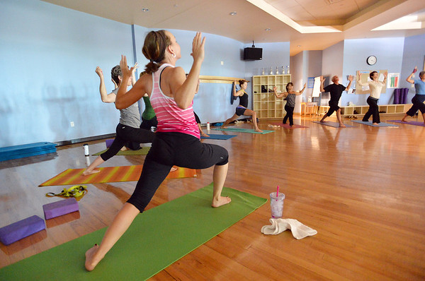 participants move into a pose during the Yoga and Tibetan singing bowls fundraiser for the family of Aurora theater shooting victims Ashely Moser and her daughter who died, Veronica, 6, at the Paul Derda Recreation Center on Sunday.August 12, 2012<br /> staff photo/ David R. Jennings