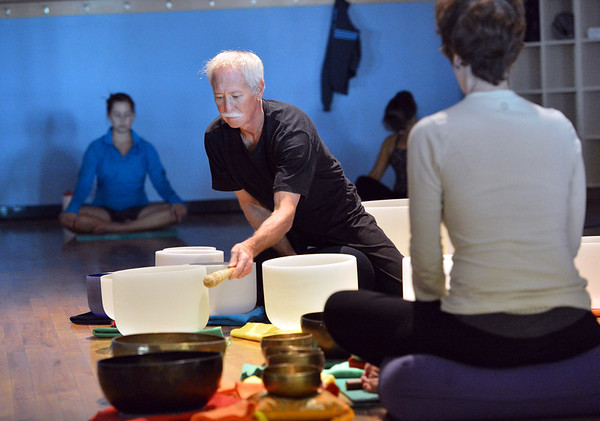 Keith Montoya, left, and his wife Vicki Ferguson play the Tibetan singing bowls during the Yoga and Tibetan Sing Bowls fundraiser for the family of Aurora theater shooting victims Ashely Moser and her daughter who died, Veronica, 6, at the Paul Derda Recreation Center on Sunday. August 12, 2012<br /> staff photo/ David R. Jennings