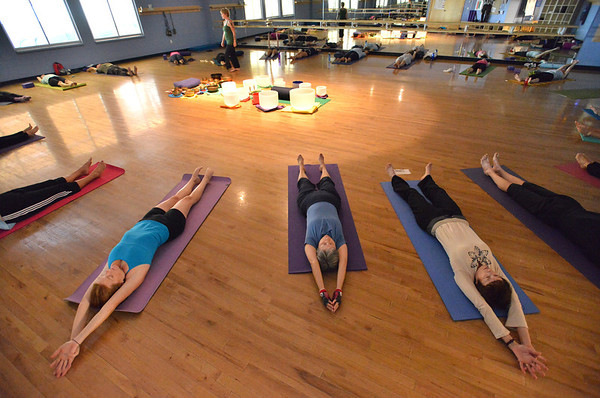 Participants go into poses during the Yoga and Tibetan singing bowls fundraiser for the family of Aurora theater shooting victims Ashely Moser and her daughter who died, Veronica, 6, at the Paul Derda Recreation Center on Sunday.August 12, 2012<br /> staff photo/ David R. Jennings