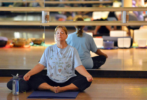 Jean Rosencrans holds a pose during the Yoga and Tibetan singing bowls fundraiser for the family of Aurora theater shooting victims Ashely Moser and her daughter who died, Veronica, 6, at the Paul Derda Recreation Center on Sunday.<br />  August 12, 2012<br /> staff photo/ David R. Jennings