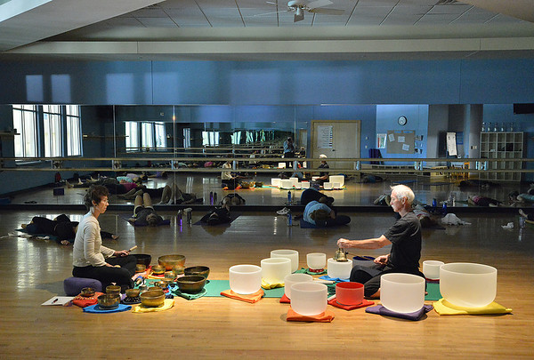 Keith Montoya, left, and his wife Vicki Ferguson play the Tibetan singing bowls during the yoga Tibetan Sing Bowls fundraiser for the family of Aurora theater shooting victims Ashely Moser and her daughter who died, Veronica, 6, at the Paul Derda Recreation Center August 12, 2012<br /> staff photo/ David R. Jennings