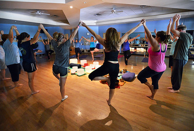 Participants hold hands while moving into a pose around the singing bowls during the Yoga and Tibetan Sing Bowls fundraiser for the family of Aurora theater shooting victims Ashely Moser and her daughter who died, Veronica, 6, at the Paul Derda Recreation Center on Sunday.August 12, 2012 staff photo/ David R. Jennings