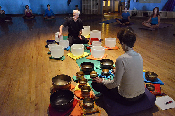 Keith Montoya, left, and his wife Vicki Ferguson play the Tibetan singing bowls during the yoga Tibetan singing bowls fundraiser for the family of Aurora theater shooting victims Ashely Moser and her daughter who died, Veronica, 6, at the Paul Derda Recreation Center August 12, 2012<br /> staff photo/ David R. Jennings