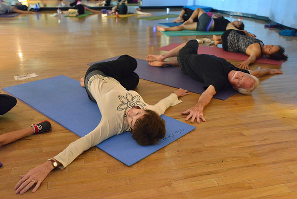 Organizers Vicki Ferguson, left, and her husband Keith Montoya perform yoga poses during the Yoga and Tibetan singing bowls fundraiser for the family of Aurora theater shooting victims Ashely Moser and her daughter who died, Veronica, 6, at the Paul Derda Recreation Center on Sunday.August 12, 2012<br /> staff photo/ David R. Jennings