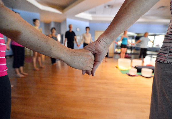 Participants hold hands for one part of the Yoga and Tibetan singing bowls fundraiser for the family of Aurora theater shooting victims Ashely Moser and her daughter who died, Veronica, 6, at the Paul Derda Recreation Center on Sunday.August 12, 2012<br /> staff photo/ David R. Jennings