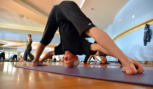 Keith Montoya goes into a yoga pose during the Yoga and Tibetan singing bowls fundraiser for the family of Aurora theater shooting victims Ashely Moser and her daughter who died, Veronica, 6, at the Paul Derda Recreation Center on Sunday.  Montoya and his wife Vicki Ferguson organized the fundraiser.<br /> August 12, 2012<br /> staff photo/ David R. Jennings