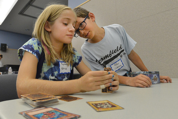 Peter Cabrera, 10, right, gives pointers to Sydney Patrick, 11, during the Yu-Gi-Ho! tournament at the Mamie Doud Eisenhower Public Library on Friday.<br /> August 10, 2012<br /> staff photo/ David R. Jennings