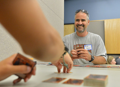 Mike Carroll, 43, plays Tomas Cabrera, 15, in the advanced play during the Yu-Gi-Ho! tournament at the Mamie Doud Eisenhower Public Library on Friday.  August 10, 2012 staff photo/ David R. Jennings