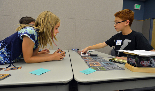 Sydney Patrick, 11, left, plays Imran Islam, 11, during the Yu-Gi-Ho! tournament at the Mamie Doud Eisenhower Public Library on Friday.<br /> August 10, 2012<br /> staff photo/ David R. Jennings