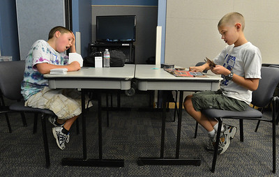 Brady Giles, 10, left, yawns while playing Ethan Cranston, 11,  during the Yu-Gi-Ho! tournament at the Mamie Doud Eisenhower Public Library on Friday. August 10, 2012 staff photo/ David R. Jennings